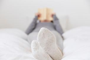 ベッドで寝ながら本を読む女性の写真素材 [FYI02823870]