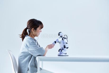 ミニロボットとおしゃべりする女性の写真素材 [FYI02823878]