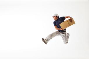 白バックの空間で荷物を持ってジャンプする作業着の男性の写真素材 [FYI02823879]
