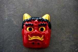 グレーの背景と赤鬼のお面の写真素材 [FYI02823884]