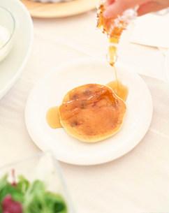 蜂蜜をかけられるパンケーキの写真素材 [FYI02823886]