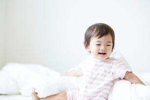 ベッドの上に座っている笑顔の赤ちゃんの写真素材 [FYI02823891]