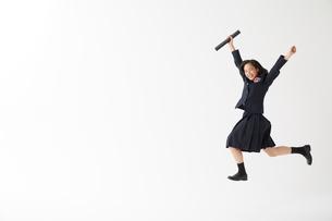 卒業証書の筒を持ってジャンプする女子高生の写真素材 [FYI02823892]
