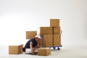 白バックの空間で台車の荷物を落として座り込む作業着の男性の写真素材 [FYI02823894]