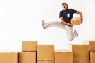 並べられたダンボール箱の後ろでジャンプする作業着の男性の写真素材 [FYI02823910]