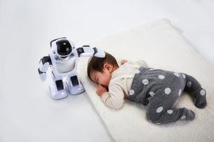 お昼寝する赤ちゃんを見守るロボットの写真素材 [FYI02823915]