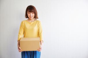 壁の前で荷物を持つ女性の写真素材 [FYI02823917]