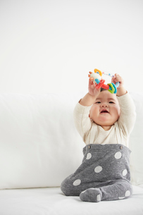 白いソファの上でおもちゃで遊ぶ赤ちゃんの写真素材 [FYI02823954]