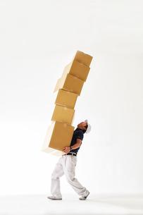 白バックの空間でたくさん重なったダンボールを運ぶ作業着の男性の写真素材 [FYI02823962]