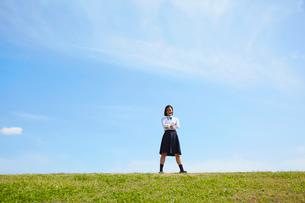 河川敷に立って腕組みをする女子高生の写真素材 [FYI02823963]