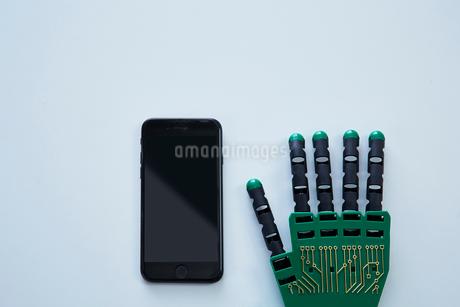 スマートフォンを触るロボットの手の写真素材 [FYI02823969]