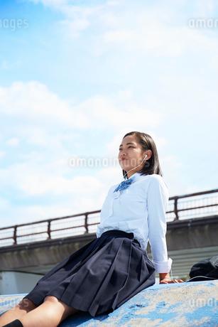 屋上でイヤホンで音楽を聴きながら寝る女子高生の写真素材 [FYI02823971]