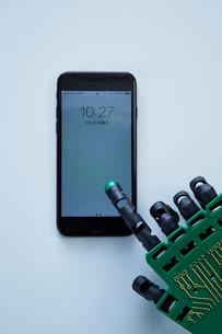 スマートフォンを触るロボットの手の写真素材 [FYI02823973]