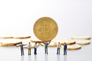 ビットコインを持ち上げるミニチュアのサラリーマンの写真素材 [FYI02823974]