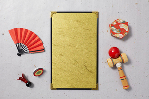 グレーの和紙に置かれた金の台紙と正月小物の写真素材 [FYI02823990]