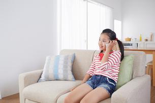 リビングソファーに座って電話をする女の子の写真素材 [FYI02823991]