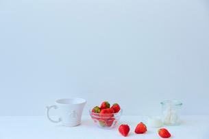 白いテーブルの上に置かれたカップとイチゴの写真素材 [FYI02823993]