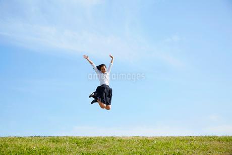 河川敷でジャンプする女子高生の写真素材 [FYI02824006]