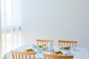 ダイニングテーブルの上に置かれた四人分の食事プレートの写真素材 [FYI02824010]
