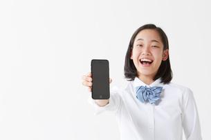 スマートフォンを片手で持って笑う女子高生の写真素材 [FYI02824029]