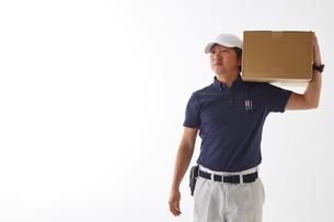 白バックの空間に立つ荷物を肩に持った作業着の男性の写真素材 [FYI02824030]