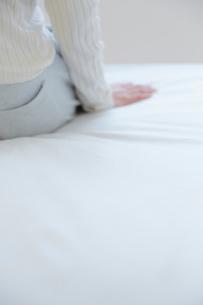 ベッドに座る女性の手元の写真素材 [FYI02824040]