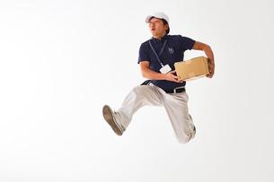 白バックの空間で荷物を持ってジャンプする作業着の男性の写真素材 [FYI02824064]