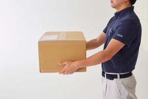 白バックの空間で荷物を両手で持つ男性の腕の写真素材 [FYI02824065]
