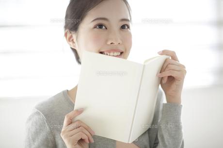 本を見る若い女性の写真素材 [FYI02824083]