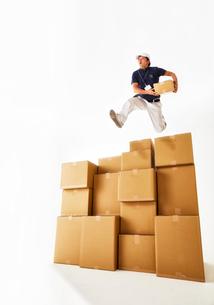 たくさん積み上げられたダンボール箱を飛び越える作業着の男性の写真素材 [FYI02824108]