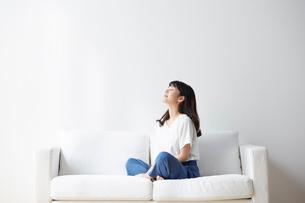 ソファの上で深呼吸する女性の写真素材 [FYI02824116]