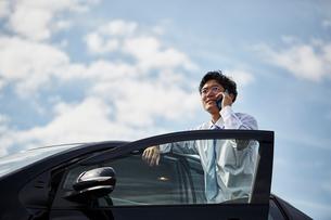 車の横に立ち電話をかける男性の写真素材 [FYI02824127]