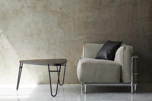 コンクリート壁と大理石床の空間に置かれたグレーのソファとローテーブルの写真素材 [FYI02824142]