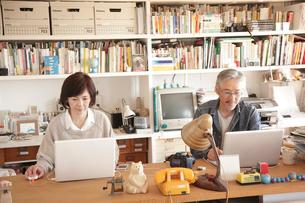 書斎でノートパソコンを見るミドル夫婦の写真素材 [FYI02824204]