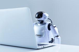 ノートパソコンを操作するミニロボットの写真素材 [FYI02824205]