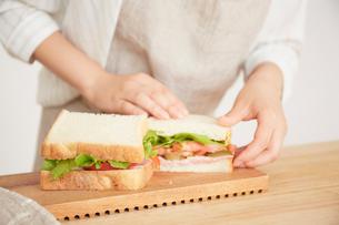 切ったサンドイッチを開く女性の写真素材 [FYI02824224]