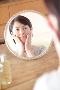 頬に手を当て鏡を見るミドル女性の写真素材 [FYI02824232]