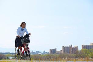 河川敷を自転車で走る女子高生の写真素材 [FYI02824237]
