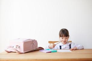 テーブルでランドセルを広げて勉強する女の子の写真素材 [FYI02824248]