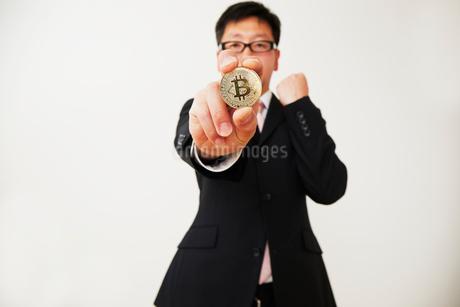 ビットコインを持ったスーツを着た男性の写真素材 [FYI02824333]