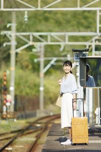 駅のホームで電車を待つ女性の写真素材 [FYI02824367]