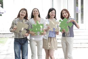 パズルピースを持つ4人の若い女性の写真素材 [FYI02824457]