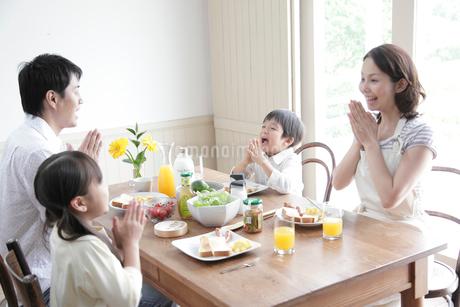 朝食で手を合わす4人家族の写真素材 [FYI02824467]