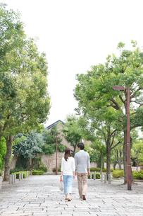新緑の住宅街を歩く後姿の若いカップルの写真素材 [FYI02824495]