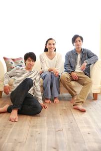 ソファに座って微笑む3人の若い男女の写真素材 [FYI02824519]