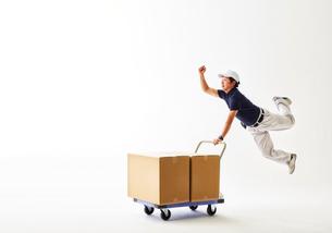 白バックの空間で荷物の乗った台車を運ぶ作業着の男性の写真素材 [FYI02824531]