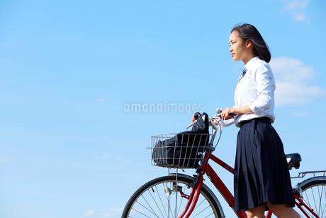 自転車を押して歩く女子高生の写真素材 [FYI02824535]
