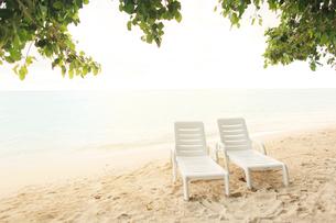 夕焼けに染まり始めたビーチに置かれたペアのイスの写真素材 [FYI02824536]