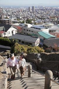街並みを見渡す公園の階段を上るミドル夫婦の写真素材 [FYI02824537]