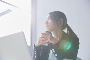 職場のデスクで窓の外を見て暗い表情をする女性の写真素材 [FYI02824586]
